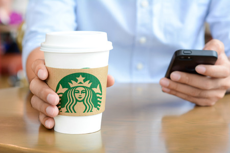 A man grabbing Starbucks paper coffee cup while using smart phone with another hand on the table in Starbucks coffee shop.