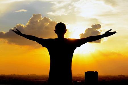 personen: Silhouet van een man hief zijn armen op twilight hemel achtergrond - gelukkig, ontspannen en succes concepten Stockfoto