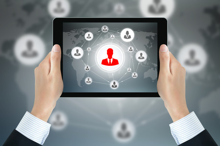 linked hands: Businessman hands holding tablet pc with businesspeople icons linked as network on the screen - online business & social network concepts Stock Photo