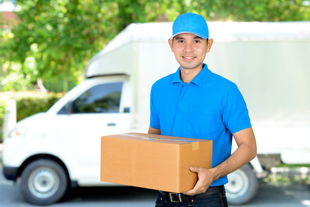 Livreur portant une boîte de colis en carton avant de la voiture de livraison