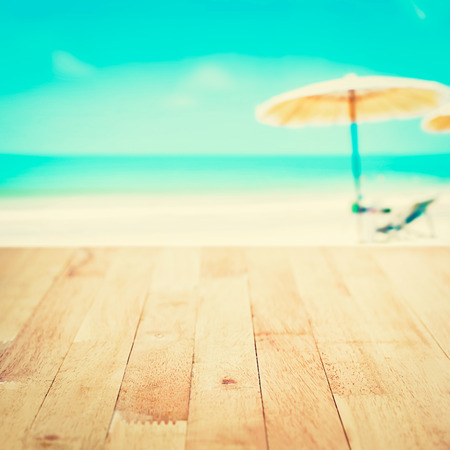 Wood table top on blurred white sand beach background, vintage tone - can be used for montage or display your products Stock Photo