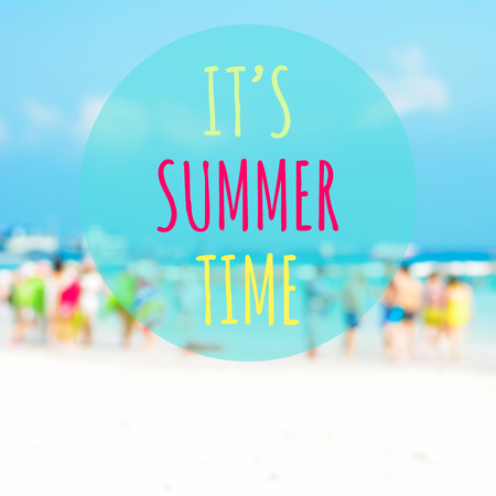 ITS SUMMER TIME text on blur beach background with people  in colorful clothes Stock Photo
