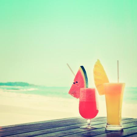 Smoothies coloridos de la fruta tropical en la tabla de madera en la playa, tono del vintage