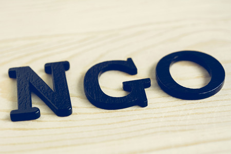 NGO letters on wood background - NGO stand for Non-Governmental Organization 免版税图像