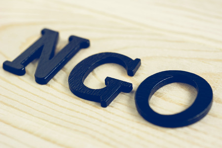 ngo: NGO letters on wood background - NGO stand for Non-Governmental Organization Stock Photo