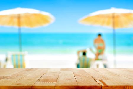 Houten tafelblad op vage witte zandstrand achtergrond met een aantal mensen - kan gebruikt worden voor montage of tonen van uw producten