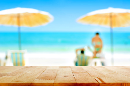 relaxing beach: Wood table top on blurred white sand beach background with some people - can be used for montage or display your products Stock Photo