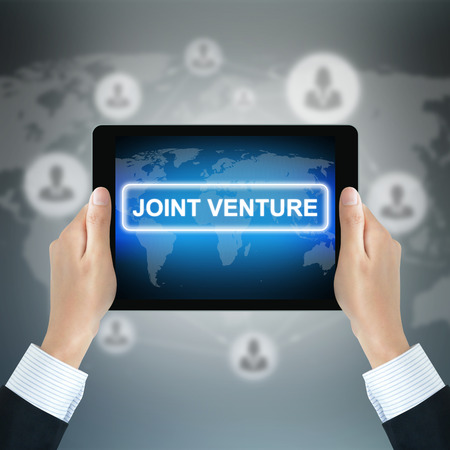 international business agreement: JOINT VENTURE sign on tablet pc screen held by businessman hands