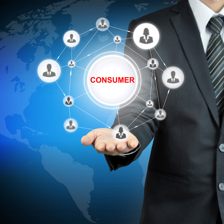 consumer: CONSUMER sign with people icon network on businessman hand Stock Photo
