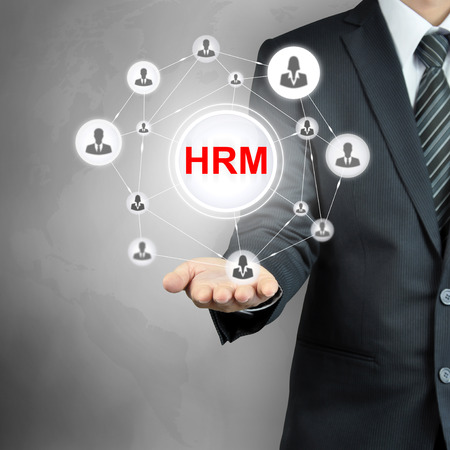 HRM (or Human Resources Management ) sign with people icons linked as network on businessman hand Stock Photo