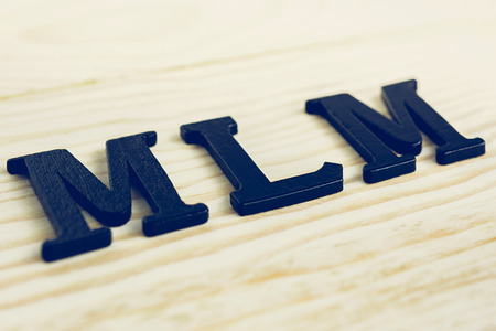 multilevel: MLM (or Multi-Level Marketing) sing on wood background Stock Photo