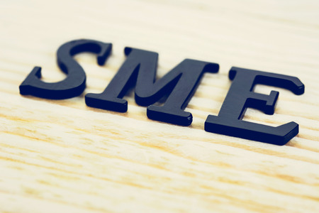 SME (or Small and Medium Enterprises) sign on wood background