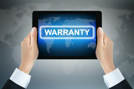 long lasting: WARRANTY sign on tablet pc screen held by businessman hands Stock Photo