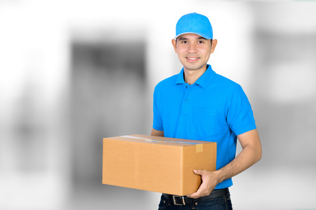 deliveryman: Deliveryman carrying a cardboard parcel box on blur white gray background