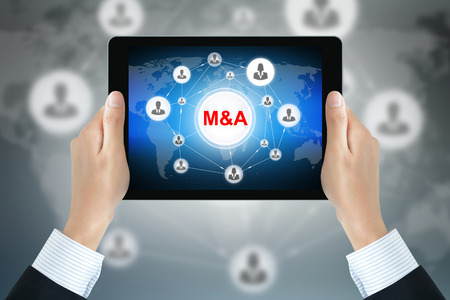 acquiring: Hands holding tablet pc with M & A (Merger & Acquisition) sign on screen
