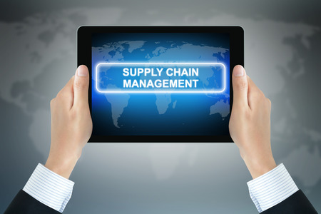 scm: SUPPLY CHAIN MANAGEMENT (or SCM) text on tablet pc screen held by businessman hands