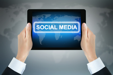 SOCIAL MEDIA sign on tablet pc screen held by businessman hands Stock Photo