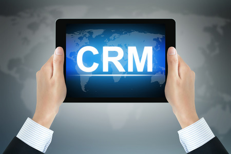 relationship strategy: CRM (or Customer Relationship Management) sign on tablet pc screen held by businessman hands Stock Photo