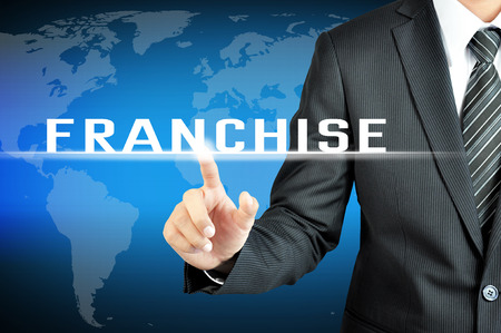 franchise: Businessman hand touching FRANCHISE sign on virtual screeen