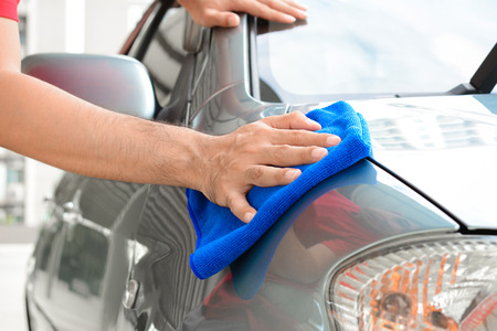 A man hand cleaning car with microfiber cloth