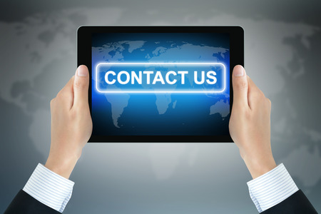 contact us sign: CONTACT US sign on tablet pc screen held by businessman hands Stock Photo