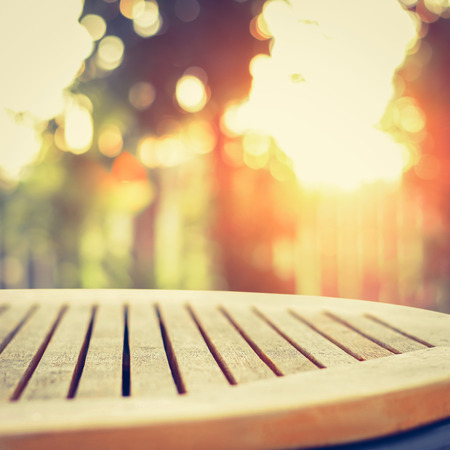 earth tone: Round wood table top on blur bokeh background of sunlight shining through the trees, vintage tone - can be used for display or montage your products