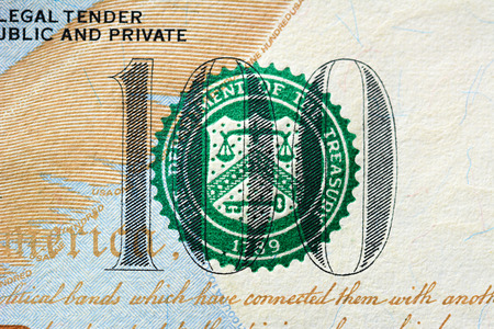 printed: Close up of number 100 with THE DEPARTMENT OF TREASURY seal on one hundred US dollar bill Stock Photo