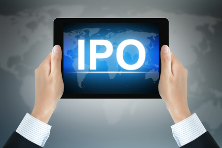 public offering: IPO (or Initial Public Offering ) sign on tablet pc screen held by businessman hands