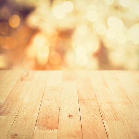 Wood table top on abstract shiny bokeh gold background, vintage tone - can be used for display or montage your products Stock Photo