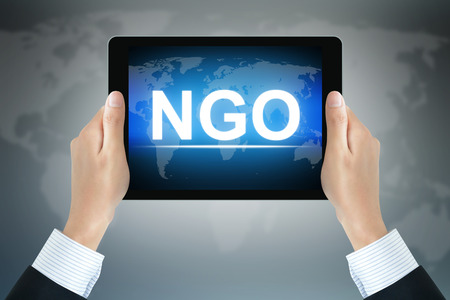 governmental: NGO (or Non-Governmental Organization) sign on tablet pc screen held by businessman hands Stock Photo