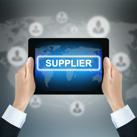 supplier: SUPPLIER text on tablet pc screen held by businessman hands