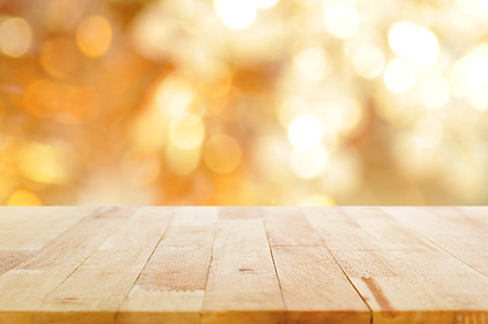 Wood table top on shiny bokeh gold background - can be used for display or montage your products Foto de archivo