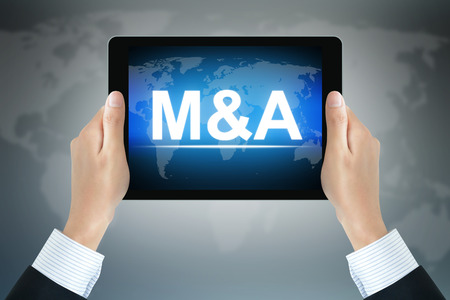 merger: Hands holding tablet pc with M & A (Merger & Acquisition) sign on screen