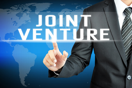 venture: Businessman hand touching JOINT VENTURE sign on virtual screen