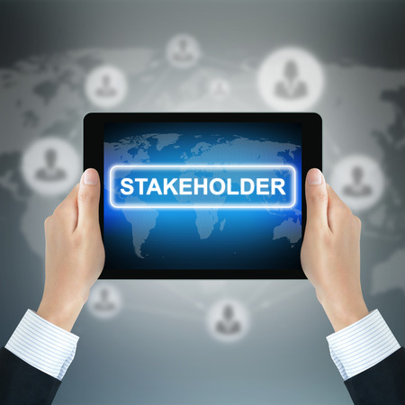 STAKEHOLDER sign on tablet pc screen held by businessman hands