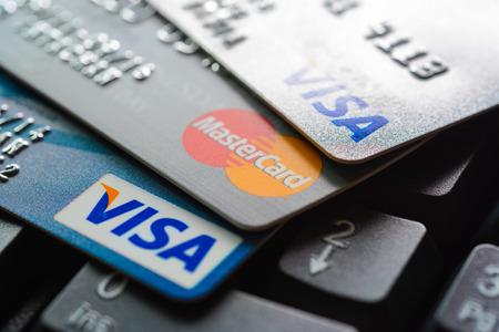 tarjeta de credito: Grupo de tarjetas de crédito en el teclado de ordenador con VISA y MasterCard logotipos de marcas Editorial