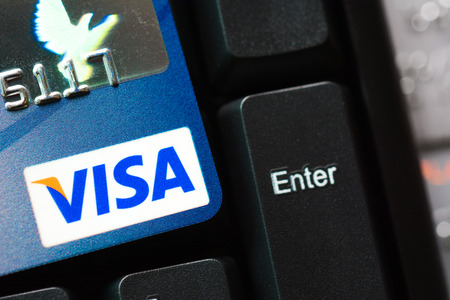 headquartered: Credit card with VISA logo on computer keyboard, VISA is an American multinational financial services corporation headquartered in California, United States.