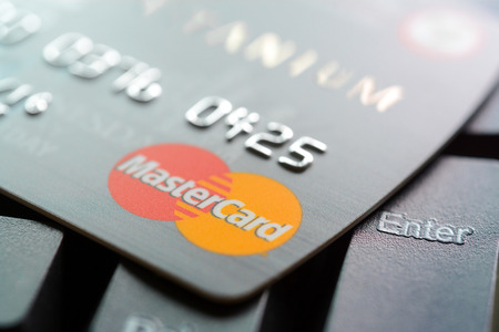 headquartered: Credit card with MasterCard logo on computer keyboard. MasterCard is an American multinational financial services corporation headquartered in New York, United States Editorial