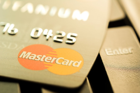 headquartered: Bangkok, Thailand - Jun 23, 2015 : Credit card with MasterCard logo on computer keyboard. MasterCard is an American multinational financial services corporation headquartered in New York, United States