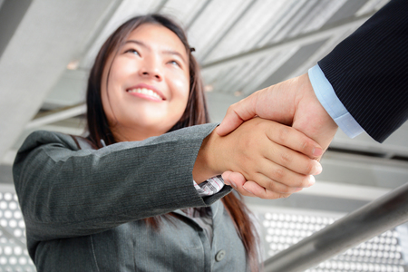 women friendship: Smiling businesswoman making handshake with a businessman Stock Photo