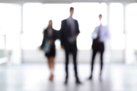 blurred: Blurred business people standing in building hall , can be used as background