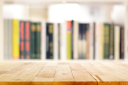 blurred: Wood table top on blur bookshelf background - can be used for display or montage your products