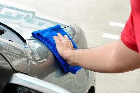 hand rubbing: Hand rubbing and polishing car with microfiber cloth Stock Photo