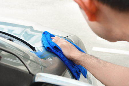 valeting: A man rubbing and polishing car with microfiber cloth Stock Photo