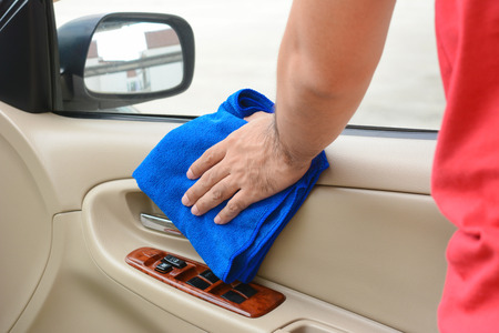 microfiber cloth: Hand cleaning interior car door panel with microfiber cloth