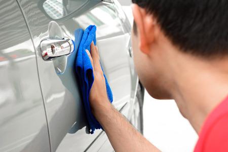 lavar: Un hombre de la limpieza del coche con un pa�o de microfibra Foto de archivo