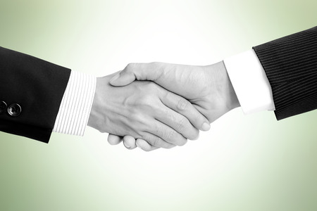 merger: Handshake of businessmen on light green background - greeting, dealing,  merger and a acquisition concepts