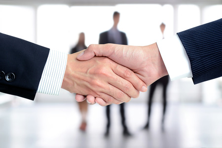 partnership: Handshake of businessmen on blur businesspeople background - greeting, dealing,  merger and a acquisition concepts