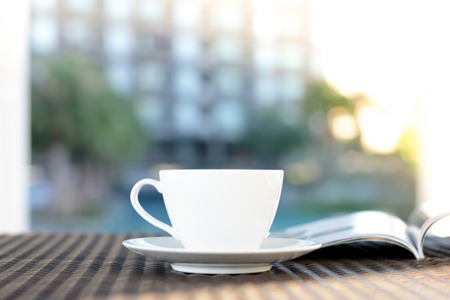 chilling out: Blurred coffee cup with opened book on outdoor rattan table in the morning - chilling out in resort or hotel concept