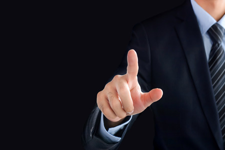 hands touch: Businessman hand pointing on empty space on black background Stock Photo